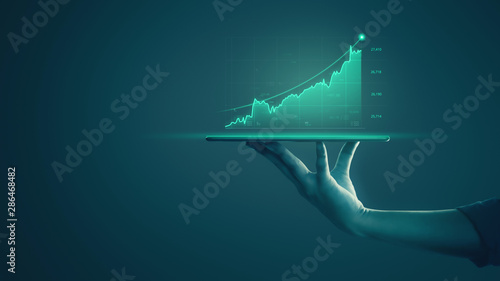 Businessman holding tablet and showing holographic graphs and stock market statistics gain profits Fototapete