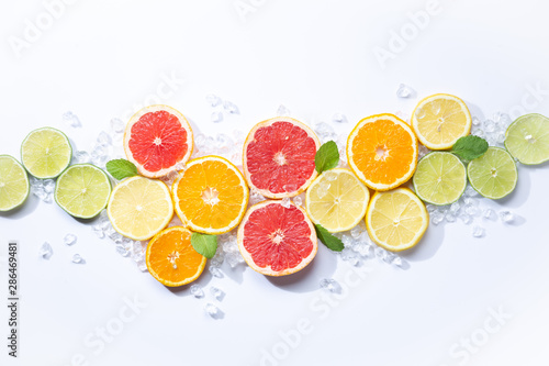 Colorful fruits backround. .citrus slices,orange, lemon, lime, and grapefruit with ice and mint. white background. Top view - 286469481