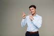 Image of cheerful brunette man wearing formal clothes smiling and pointing finger aside at copyspace