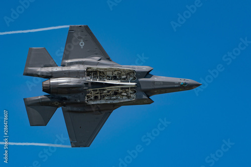 F35 Lightning II Jet Fighter with banking with bomb doors open close up against blue sky