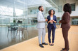 Serious multiracial business colleagues talking. Full length view of male and female business people in formal wear standing together and interacting. Cooperation concept