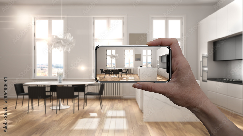 Fototapeta Hand holding smart phone, AR application, simulate furniture and interior design products in real home, architect designer concept, blur background, modern white and gray kitchen