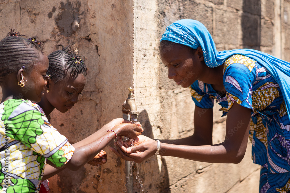 Fototapety, obrazy: Three Gorgeous African Girls Around a Tap to Get some Water