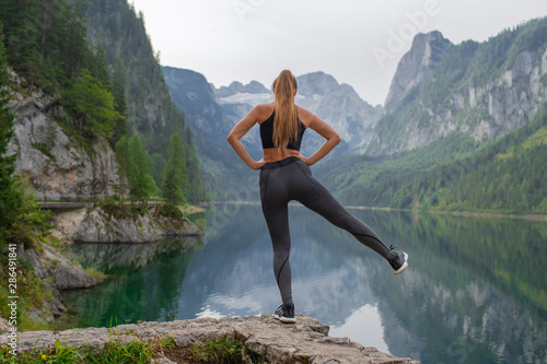 Young sexy athletic girl in the mountains near the lake