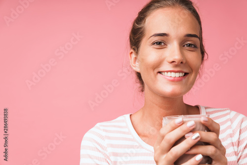 Fotografia Image closeup of lovely gorgeous woman smiling and holding chocolate milk in gla
