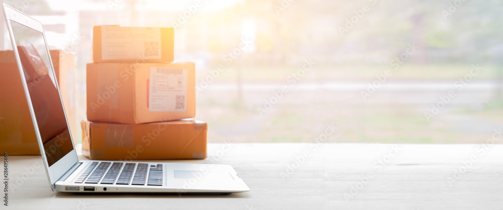 Fototapety, obrazy: Laptop computer at workplace of start up, small business owner. cardboard parcel box of product for deliver to customer. Online selling, e-commerce, packing concept, Morning light,blurred image