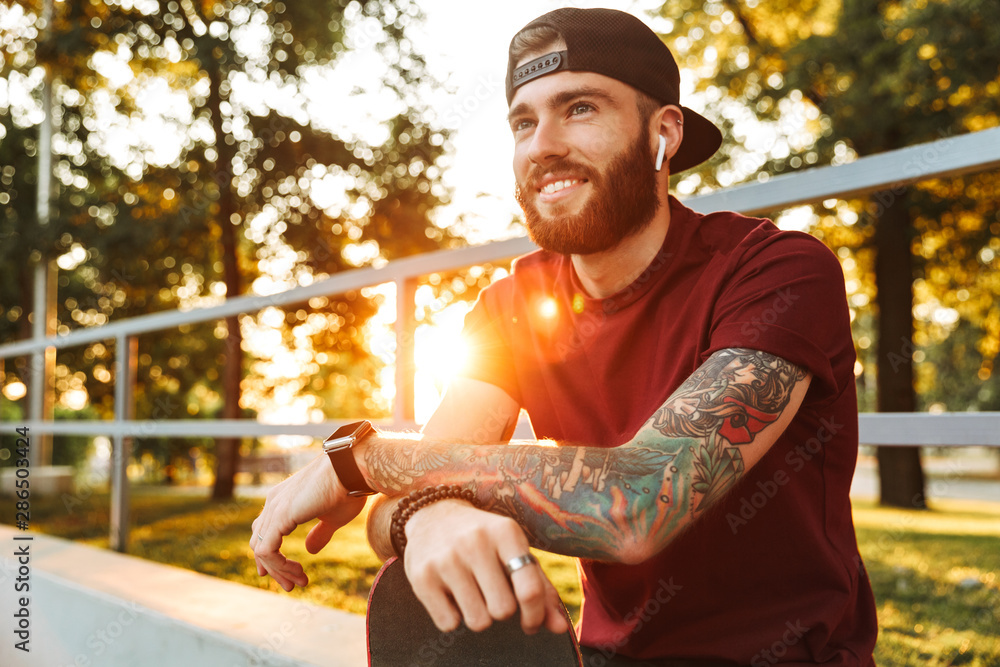 Fototapeta Attractive cheerful young man sitting at the skate park ramp