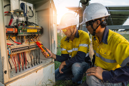 Fotografering Workers use clamp meter to measure the current of electrical wires produced from