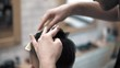 Close up on Men's hairstyling and haircutting in a barber shop or hair salon using scissors and hair dryer. Grooming the hair. Barbershop.
