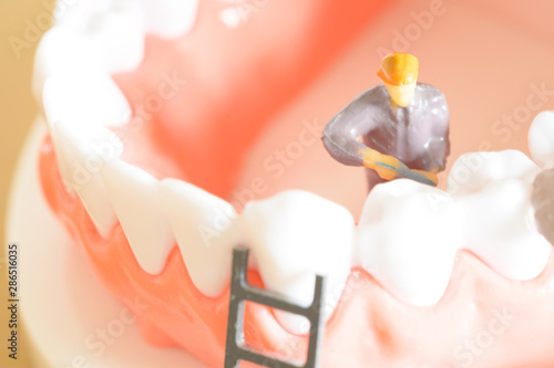 Miniature worker model cleaning teeth for dental clinic, good health care demons Canvas Print