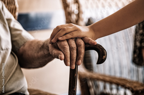 child's hand over old man's hand holding a cane. Wallpaper Mural