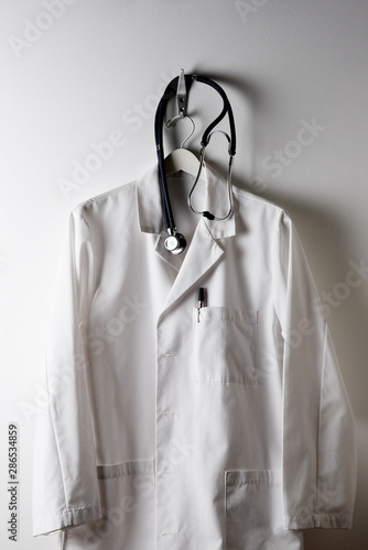 Obraz na plátne A Doctors White Lab Coat on a hanger and hook with Stethoscope.
