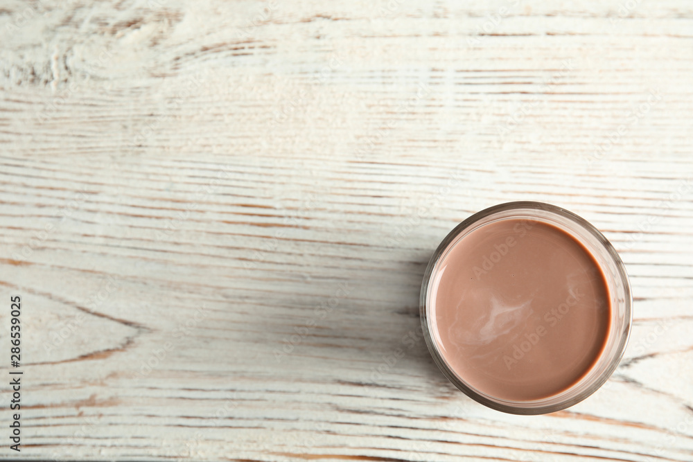 Fototapety, obrazy: Glass of tasty chocolate milk on wooden background, top view with space for text. Dairy drink
