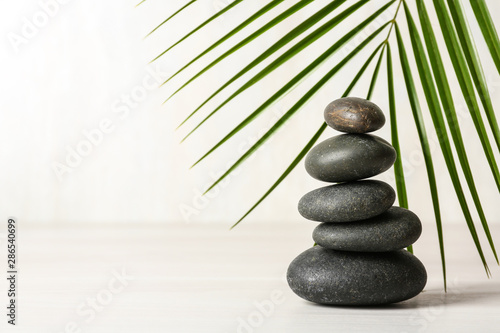 Photo Stack of spa stones and palm leaf on table against white background, space for t