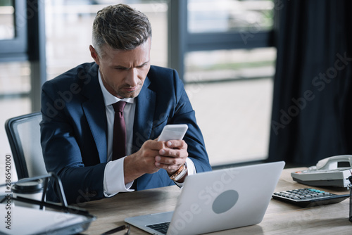 Foto auf Leinwand Texturen handsome businessman using smartphone near laptop and document tray