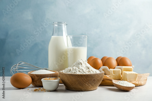 Photographie Fresh ingredients for delicious homemade cake on white wooden table against blue