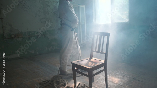 Two psycho men going around chair in mental hospital Fototapeta