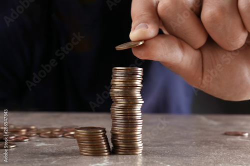 Photo Man stacking coins on brown marble table, closeup