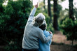Couple of mature senior old people hug and enjoy the outdoor leisure activity together in the forest - green trees in background - unrecognizable man and woman for elderly healthy ilfestyle