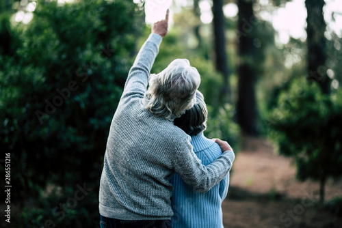Fototapeta Couple of mature senior old people hug and enjoy the outdoor leisure activity together in the forest - green trees in background - unrecognizable man and woman for elderly healthy ilfestyle obraz