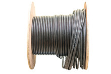 Roll Of Outdoor Fiber Optic Signal Shielded Cable Is On A White Background. Wooden Coils Of Powerful Black Telecommunications Wire. Many Turns Of The Main Electrical Cable.