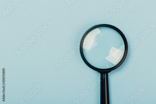 Photo Small magnifying glass on pastel blue background