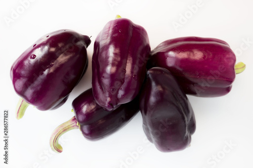 five violet peppers on a white background