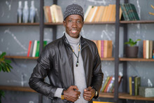 Close Up Portrait Of A Confident Young African Man In Blck Leather Jacket Indoors Smiling