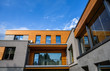 Leinwanddruck Bild - Modern new house exterior, facade with natural wood and many windows on blue sky background