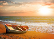 Small Boat On A Sandy Sea Beach At The Sunset