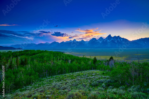 Fotobehang Donkerblauw Colorful clouds with sunset at the Grand Teton mountain range.