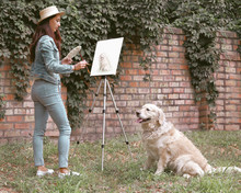 Collage With Portrait Of Young Pretty Woman In A Hat Standing And Painting Picture Of Dog Golden Retriever Using Brushes And A Modern Easel Outdoor.