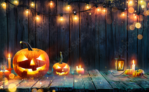 Obraz na plátně Halloween - Jack O' Lanterns - Candles And String Lights On Wooden Table