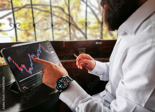 Fototapeta Smoking young bearded adult male with tablet pro and smart watch checking the market stock exchange forex cryptocurrency in the cafe pub obraz na płótnie