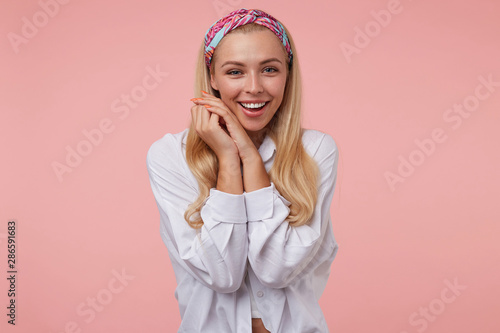 Photo Indoor shot of young attractive woman with crossed palms near her face looking t