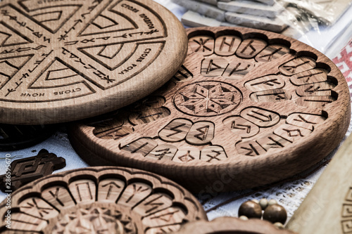 Wooden household items with ancient Slavic Nordic handmade symbols crests, runes, hats Canvas Print