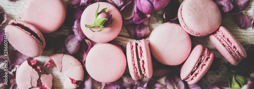 Flat-lay of sweet pink macaron cookies and rose buds and petals over wooden background, top view, close-up, wide composition. Food texture, background and wallpaper