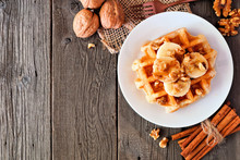Breakfast Waffle With Bananas, Walnuts And Syrup. Top View Corner Border With Copy Space Over A Wood Background.