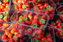 Plastic Punnets Of Ripe Strawberries For Sale On A Market Stall