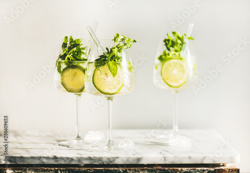Hugo Sparkling wine cocktail with fresh mint and lime in glasses with eco-friendly straws over white marble counter, selective focus. Cold refreshing summer alcoholic drink