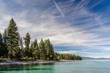 USA, California, El Dorado County, D.L. Bliss State Park. The Shoreline And Green Waters Of Lake Tahoe On A Day With Whispy Clouds.