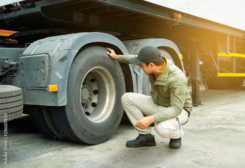 Obraz na plátně  truck driver inspecting safety check of a truck tires.