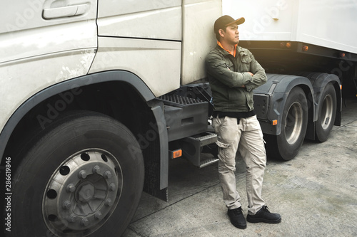 Fotografie, Obraz  Portrait of truck driver looking cross one's arm with a semi truck