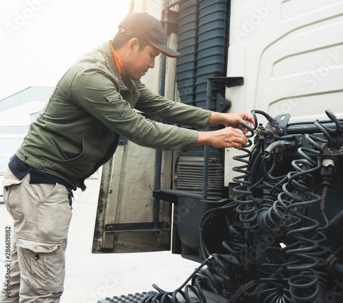 Fotografie, Obraz  truck driver inspecting safety check hydraulic cable of a semi truck
