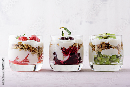 Fototapeta healthy dessert with whipped cottage cheese, granola, strawberries, cherries and kiwi on pink background obraz