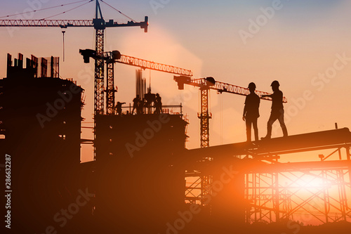 Obraz Silhouette Two engineers consult and inspect high-rise construction work over blurred industry background with Light fair.Create from multiple reference images together - fototapety do salonu