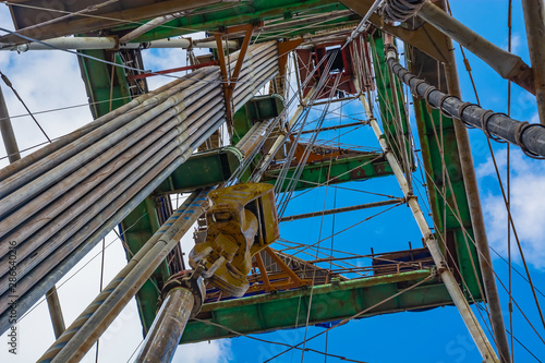The location of the equipment inside the drilling rig for oil and gas drilling. Vertical stand drill pipes. Lifting system. Bottom-up view. Blue cloudy sky.