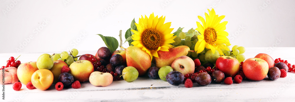 Autumn nature concept. Fall fruit with grapes, plums and sunflower on wood. Thanksgiving dinner