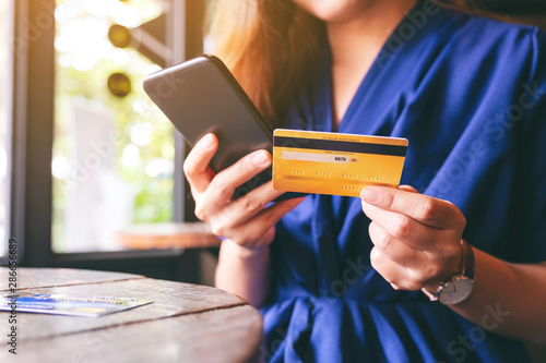 Fotografía  Closeup image of asian woman using credit card for purchasing and shopping onlin