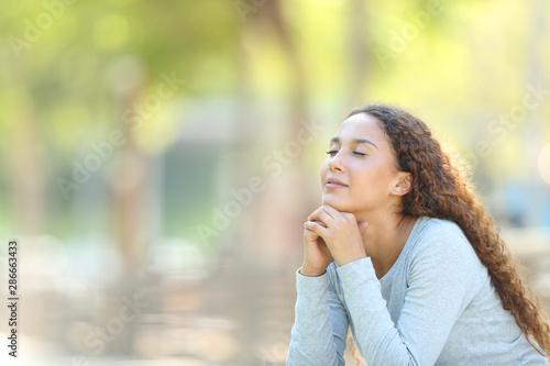 Fotografia Mixed-race woman relaxing meditating in a park